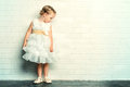 Angelic girl little in a beautiful white dress standing by the white brick wall childhood Stock Photos