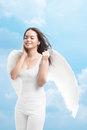 Angelic pleasure vertical shot of a winged girl listening to music with Royalty Free Stock Photos