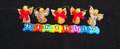 Angels and birthday text in white letters on colorful jigsaw style colorful pieces with above isolated on black background with Stock Image