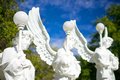 Angels with lamps statues of white colored holding a pole lamp the blue skies and green trees in the background Stock Photography