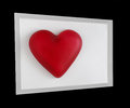 Angled framed red heart photograph of glass box inside gray black frame Stock Photos