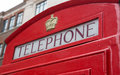Angled red telephone booth sign an view of a in london england Royalty Free Stock Photography
