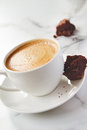 Angled view of cappuccino or latte coffee with chocolate brownie cookie on marble table Royalty Free Stock Photo