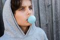 Angled view of teenage boy blowing blue bubble gum Royalty Free Stock Photo