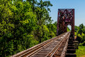 Angled view of a train track and old iconic truss bridge an railroad trestle with an iron over the brazos river texas Stock Images