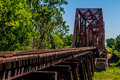 Angled view of a train track and old iconic truss bridge an railroad trestle with an iron over the brazos river texas Royalty Free Stock Image