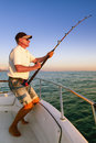 Angler fisherman fighting big fish from the boat on ocean Stock Photos