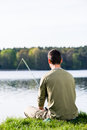 Angler sitting in grass at lake fishing with his rod a very peaceful scene Stock Photography