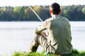 Angler sitting in grass at lake fishing with his rod a very peaceful scene Royalty Free Stock Images