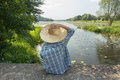 Angling boy with fishing rod holding with one hand straw hat is Stock Photos