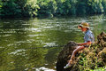 Angling kid by river young child sitting the on a wood log with an fishing rod lot cantal aveyron france landscape orientation Stock Image