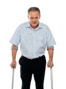 Angry aged man with crutches looking at you Stock Photography
