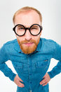 Angry amusing young man with beard in funny round glasses Royalty Free Stock Photo