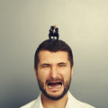 Angry boss screaming at crying man small big men over grey background Stock Images