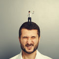 Angry boss screaming at worker small standing on the head and Royalty Free Stock Image