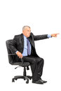 Angry boss sitting in armchair and pointing Royalty Free Stock Photos