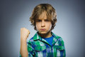 Angry boy isolated on gray background. He raised his fist to strike. Closeup