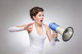 An angry bride shouting with a megaphone young and brunette caucasian in white dress the image is taken on grey gradient Royalty Free Stock Photography