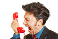 Angry business man screaming into phone receiver loudly a red Stock Photos