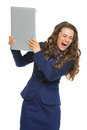 Angry business woman breaking laptop isolated on white Stock Photo