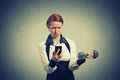 Angry business woman reading news e-mail on mobile phone lifting dumbbell Royalty Free Stock Photo
