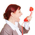 Angry business woman screaming loudly in a red phone receiver Royalty Free Stock Photography