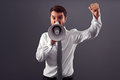 Angry businessman clenching his fist shouting megaphone Stock Photography