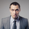 Angry businessman on gray background young Stock Photo
