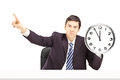 Angry businessman holding a clock and gesturing with his finger isolated on white background Royalty Free Stock Photo