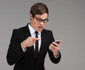 Angry businessman with mobile phone furious young holding a and pointing it while isolated on grey Stock Image