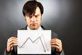 Angry businessman showing a falling graph of stock market against gray Stock Photo