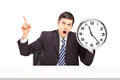 Angry businessman sitting and holding a wall clock Royalty Free Stock Photos