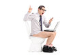 Angry businessman yelling at his phone seated on a toilet isolated on white background Royalty Free Stock Photos