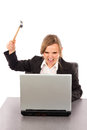 Angry businesswoman with a hammer ready to smash her laptop whil while sitting at office desk isolated on white Stock Photos
