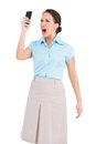 Angry classy businesswoman shouting at her smartphone on white background Royalty Free Stock Image