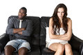 Angry couple anger emotions mixed race men and women on sofa Royalty Free Stock Photography