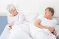 Angry couple lying on bed senior looking at each other Stock Photography