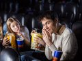 Angry daughter looking to father using mobilephone giving shh expression in movie theater Royalty Free Stock Images
