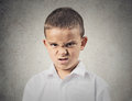 Angry disgusted boy closeup portrait displeased child looking at you camera mad about something isolated grey wall background Royalty Free Stock Photo