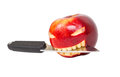 Angry face is carved on an apple and a knife Royalty Free Stock Photo