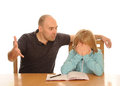 Angry father sitting desk daughter upset trying unsuccessfully to do her homework white background Stock Photo