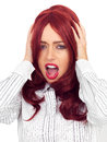 Angry frustrated red haired young woman screaming attractive with long hair in her twenties and afraid shouting or with her Stock Photo