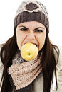 Angry girl holds apple in mouth. Winter style Stock Photography