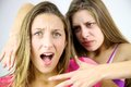 Angry girl willing to strangle blond screaming friend teenagers fighting unhappy about problems Stock Image