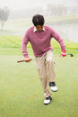 Angry golfer trying to brake his club at the golf course Stock Photo