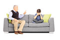 Angry grandfather shouting at his nephew seated on a sofa isolated white background Stock Photos