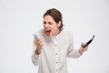 Angry irritated young business woman holding mobile phone and shouting Royalty Free Stock Photo