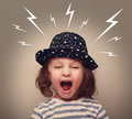 Angry kid in hat screaming white lightnings above Royalty Free Stock Photo
