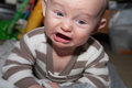 Angry little baby with blue eyes crying and disgusted expression up close Stock Images