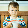 stock image of  Angry little boy drinking milk